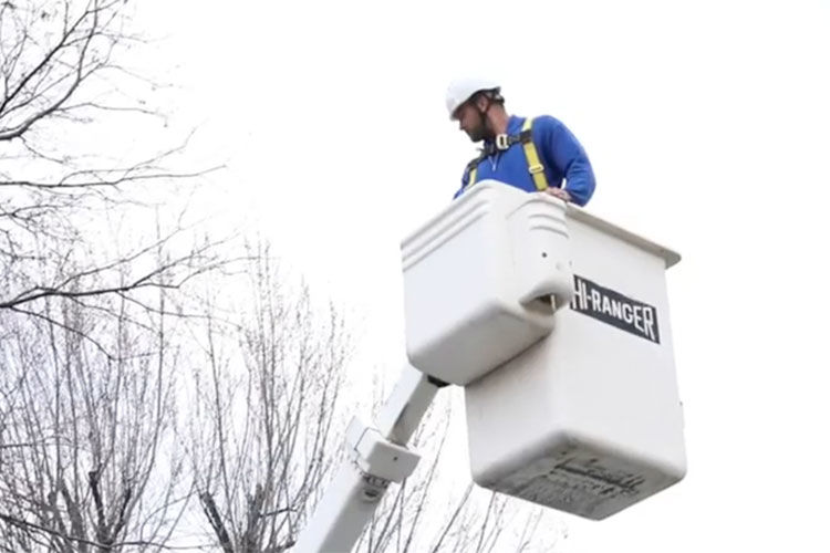 Telecommunications contractor in man lift on work truck