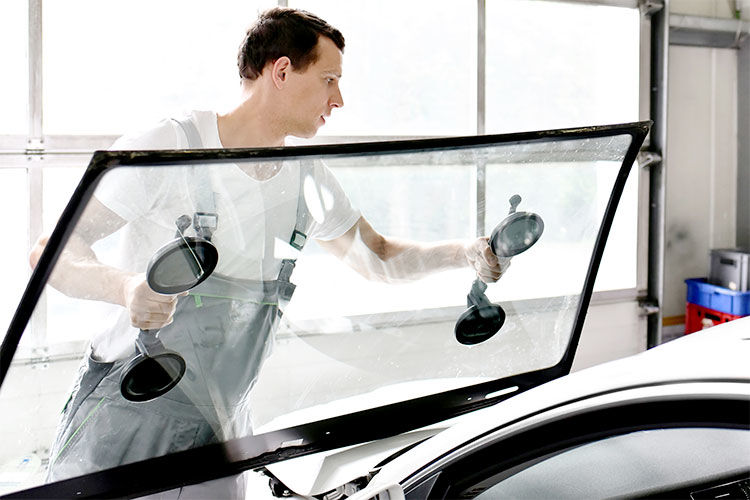 Auto glass repair technician replacing windshield