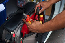 Electrician reaching into tool bag