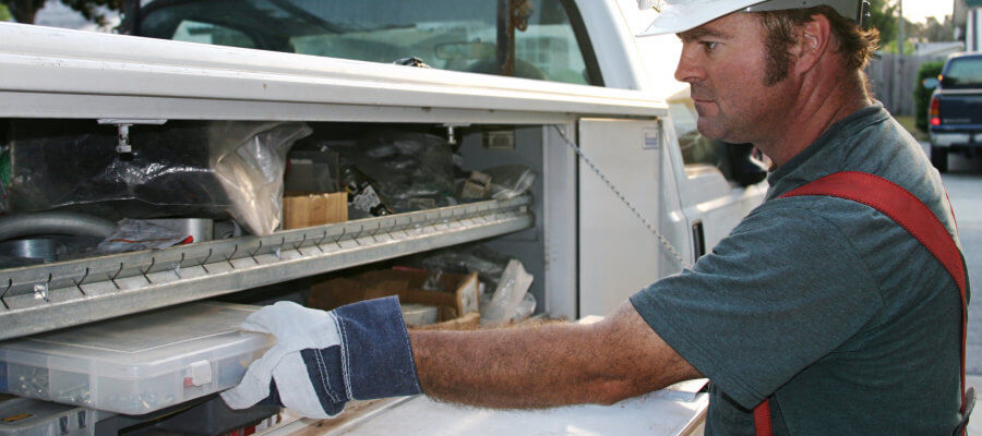 Electrician storing equipment on his work truck